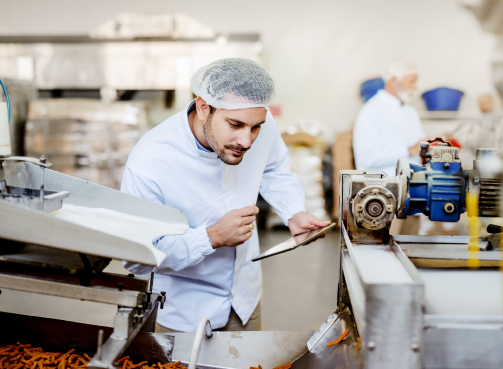 young-caucasian-serious-supervisor-evaluating-quality-food-food-plant-while-holding-tablet-man-is-dressed-white-uniform-having-hair-net 1